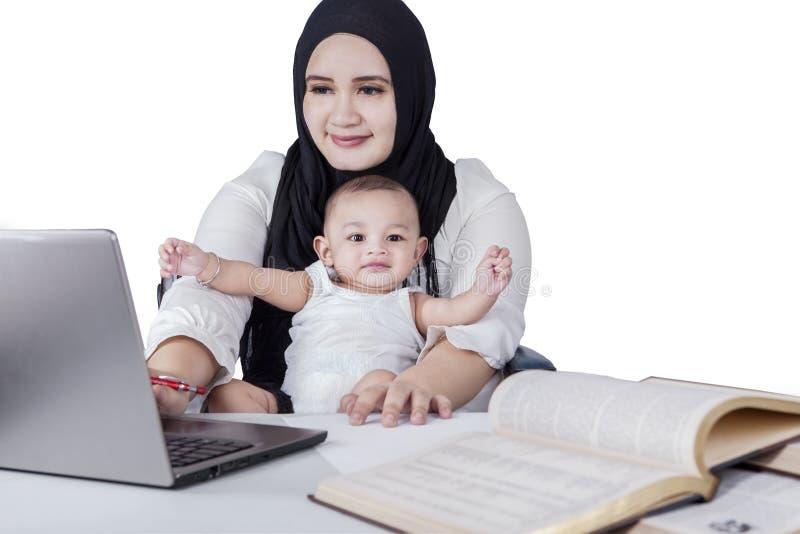 Den upptagna modern som använder bärbara datorn med henne, behandla som ett barn arkivbilder