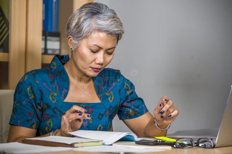 Den upptagna och koncentrerade attraktiva mitt åldrades den asiatiska kvinnan som arbetar på skrivbordet för kontorsbärbar datord fotografering för bildbyråer