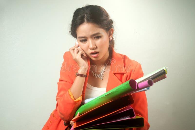 Upptagen asiatisk affärskvinna med mappar för en radda och färgrik legitimationshandlingar på bakgrund. arkivbild