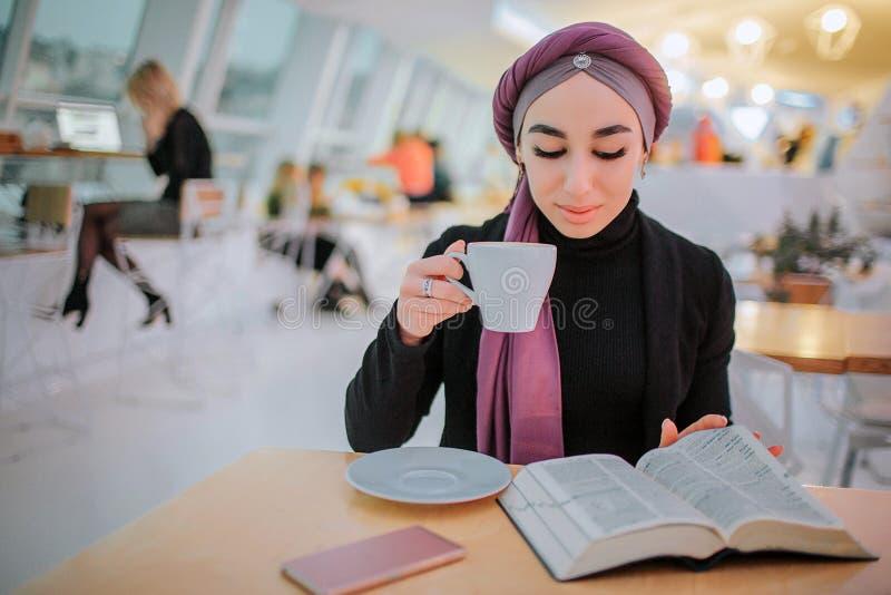 Den upptagna unga arabainkvinnan läste bok- och drinkkaffe Henne det vändande bild Hon sitter i sida Kvinnan är upptagen arkivfoto