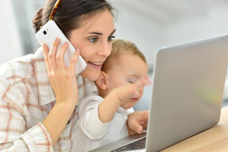 Den upptagna unga kvinnan på bärbara datorn som rymmer henne, behandla som ett barn arkivbild