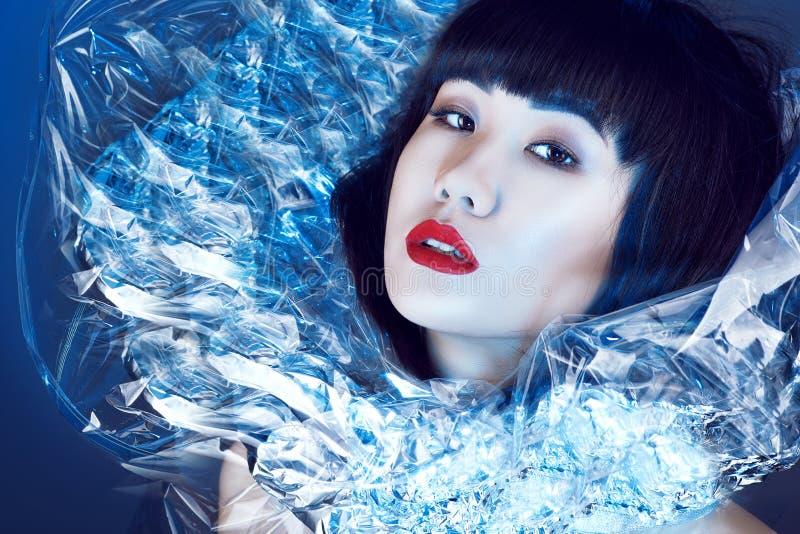 Den ursnygga asiatiska modellen med härligt smink och moderiktig frisyr med frans som bär den utsmyckade glänsande ställningen-up royaltyfri bild