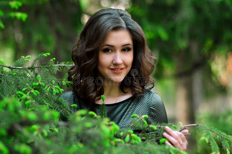 Den ursnygga, attraktiva, härliga, nätta trevliga flickan i grön klänning med perfekt makeup och frisyren i sommar, vårskog, park arkivfoto