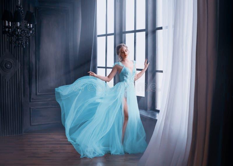 Den ursnygga bilden av kandidaten i 2019, flicka i lång blå försiktig flygaklänning med det kala benet står bara, den sagolika pr royaltyfria foton