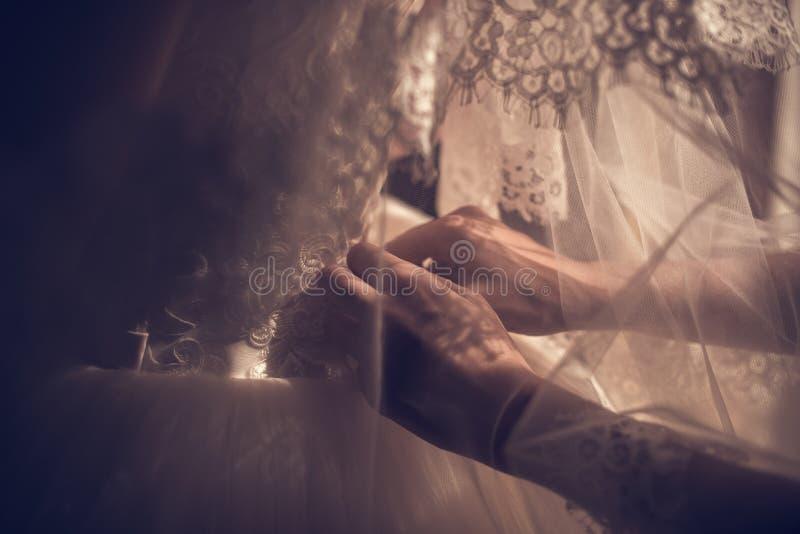 Den ursnygga blonda bruden i den vita lyxiga kl?nningen f?r klar f?r att gifta sig Morgonf?rberedelser Kvinna som s?tter p? kl?nn royaltyfri bild