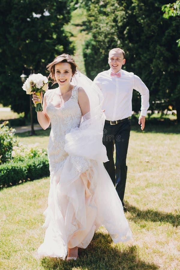 Den ursnygga bruden, i att förbluffa kappan och den stilfulla brudgummen som kör och skrattar i soligt, parkerar Härliga lyckliga royaltyfri bild
