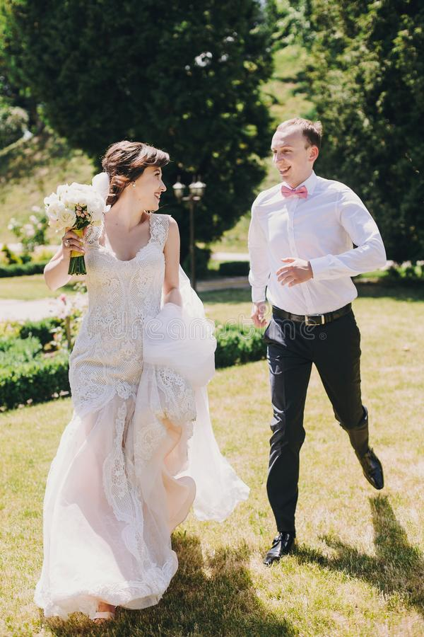 Den ursnygga bruden, i att förbluffa kappan och den stilfulla brudgummen som kör och skrattar i soligt, parkerar Härliga lyckliga royaltyfria foton