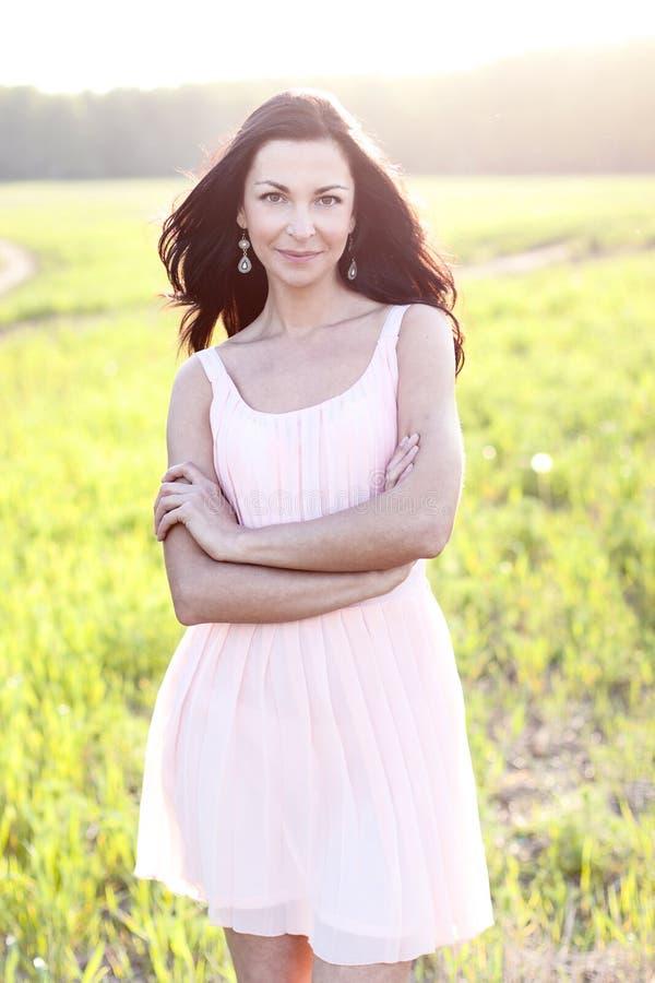 Den ursnygga brunettkvinnan med för rosa färgklänning för mörkt hår sommar parkerar den gröna ängen som ljus ferie för begreppet  royaltyfria foton