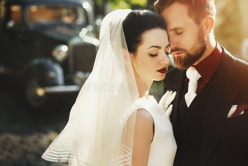 Den ursnygga eleganta bruden och stilfulla brudgummen som omfamnar, stillar handlag royaltyfria bilder