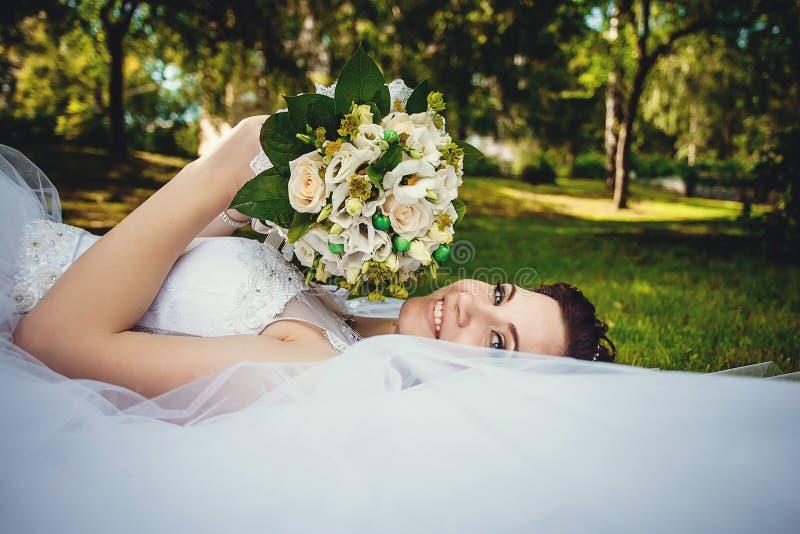 Den ursnygga härliga bruden i en vit klänning som ligger på det gröna gräset i, parkerar med en bukett av blommor i hennes händer royaltyfria foton