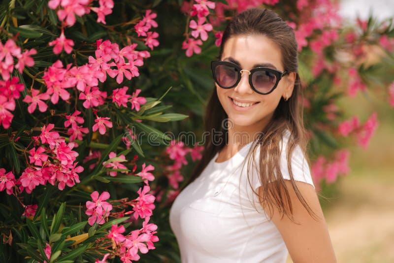 Den ursnygga kvinnan i solglasögon står i härliga blommor Stående av den lyckliga log unga kvinnan royaltyfri foto
