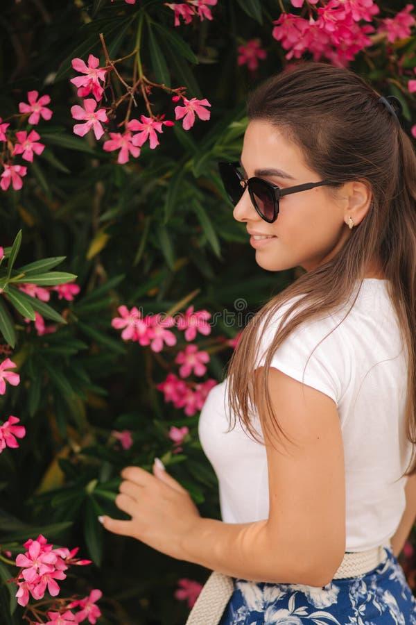 Den ursnygga kvinnan i solglasögon står i härliga blommor Stående av den lyckliga log unga kvinnan arkivfoto