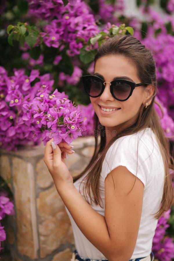 Den ursnygga kvinnan i solglasögon står i härliga blommor Stående av den lyckliga log unga kvinnan arkivbild