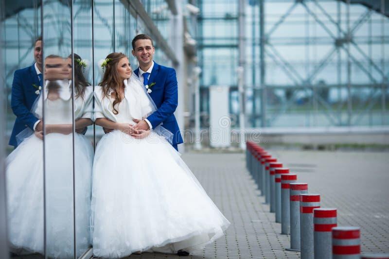 Den ursnygga lyckliga brunettbruden och den eleganta brudgummen i blått passar kramen arkivfoto