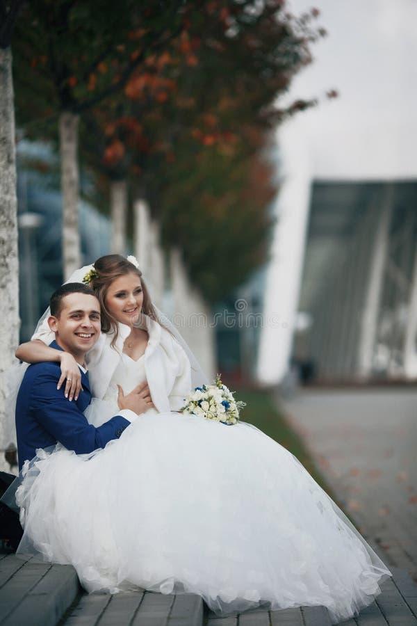 Den ursnygga lyckliga brunettbruden och den eleganta brudgummen i blåttdräkt sitter arkivfoto