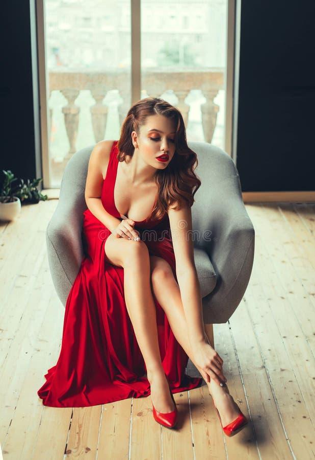 Den ursnygga rödhåriga unga kvinnan trycker på sexually hennes kala ben som visar urringningen i en dyr lång scharlakansrött läng royaltyfri bild