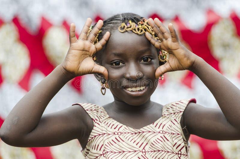 Den ursnygga unga afrikanska flickavisningen gömma i handflatan som ståenden för fredsymbolet royaltyfri fotografi