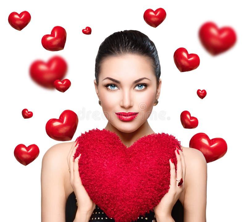 Den ursnygga unga brunettkvinnan med hjärta formade den röda kudden Valentine dag royaltyfri bild