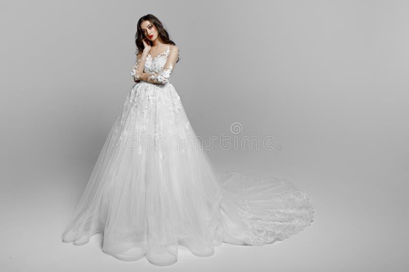 Den ursnygga unga kvinnan med lockigt långt hår i den vita bröllopsklänningen, utgör, isolerat på en vit bakgrund kopiera avst?nd royaltyfri fotografi