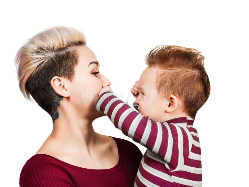 Den utöver det vanliga modern med behandla som ett barn pojken på händer med frisyren som ler som isolerar på vit bakgrund Litet  royaltyfri fotografi