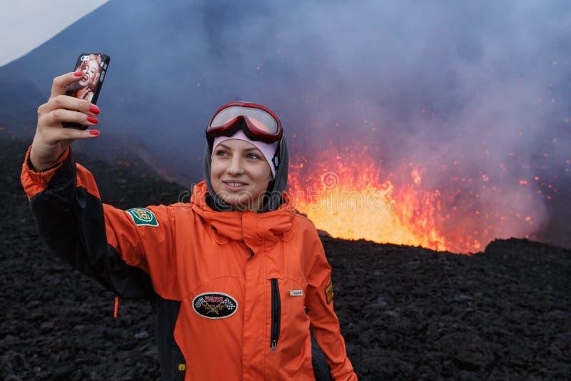 Den utbrottTolbachik vulkan på Kamchatka, flicka fotograferade selfie på bakgrundslavasjön i kratervulkan royaltyfria bilder