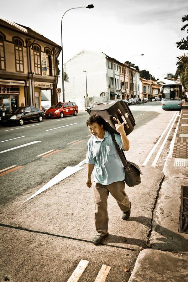 Den utländska kinesiska mannen bär ett stort bagage på vägen längs gatan av Singapore fotografering för bildbyråer