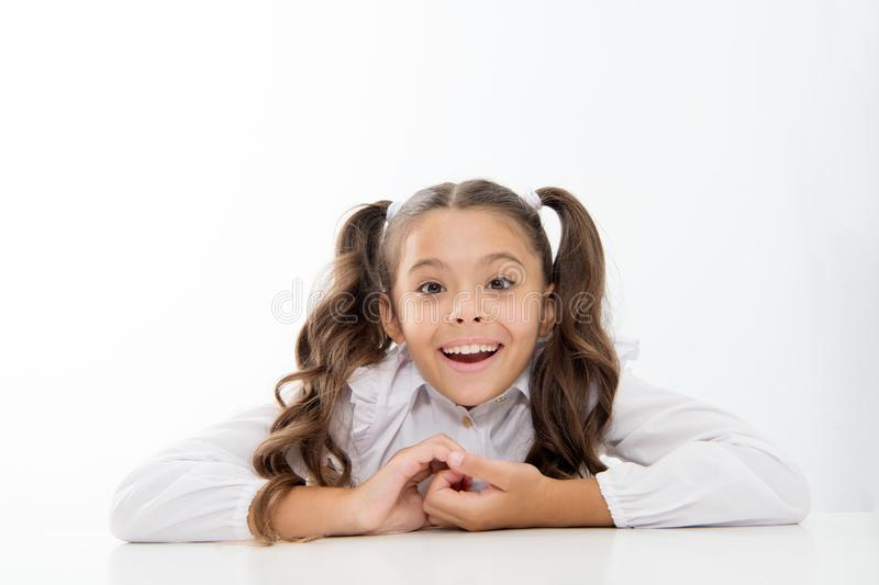 Den utmärkta eleven lutar på skrivbordet isolerad vit Perfekt skolflicka med rumsrent utsmyckat hår Ultimat bästa lista för skola fotografering för bildbyråer