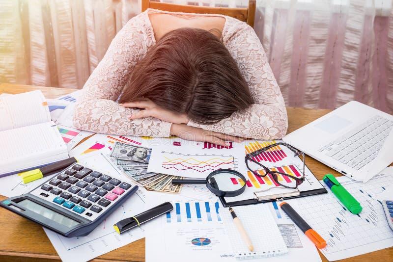 Den utmattade affärsanalytikeren sover på hennes arbetsplats royaltyfri bild