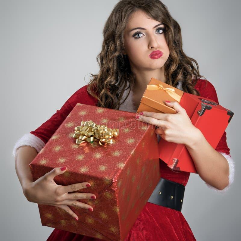 Den utmattade gulliga jultomtenhjälpredakvinnan förkrossade bärande julgåvaaskar royaltyfri fotografi