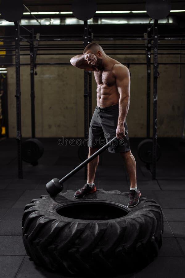Den utmattade idrottsmannen moppar hans krön efter hård utbildning royaltyfri foto