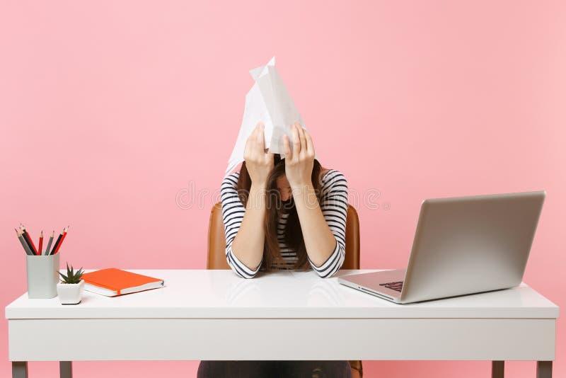 Den utmattade kvinnan som rymmer pappers- dokument nära huvudet, lutar på handarbete på projekt, medan sitta på kontoret med bärb arkivfoto