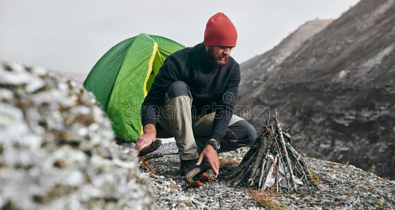 Den utomhus- horisontalbilden av den unga mannen för fotvandraren förbereder fruncher för brasa i berg Handelsresandeman med skäg arkivbilder