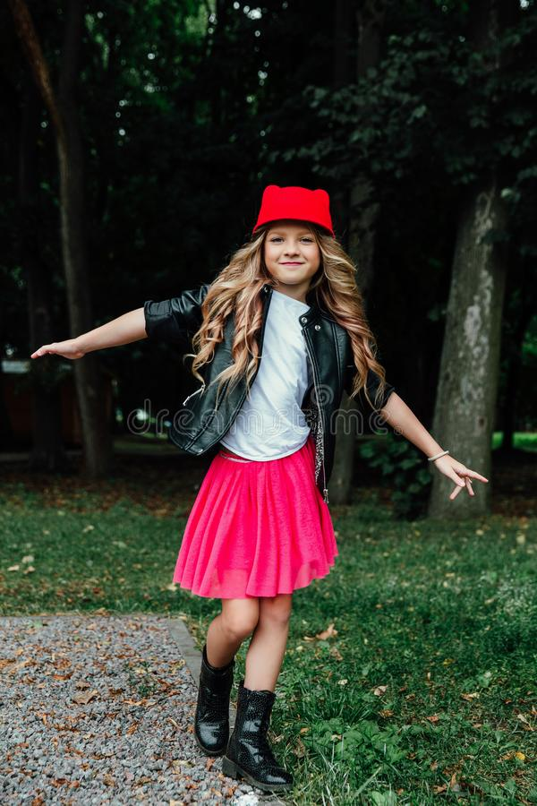 Den utomhus- livsstilståenden av den stilfulla liten flickatonåringen på stad parkerar Härligt barn som bär arkivfoto