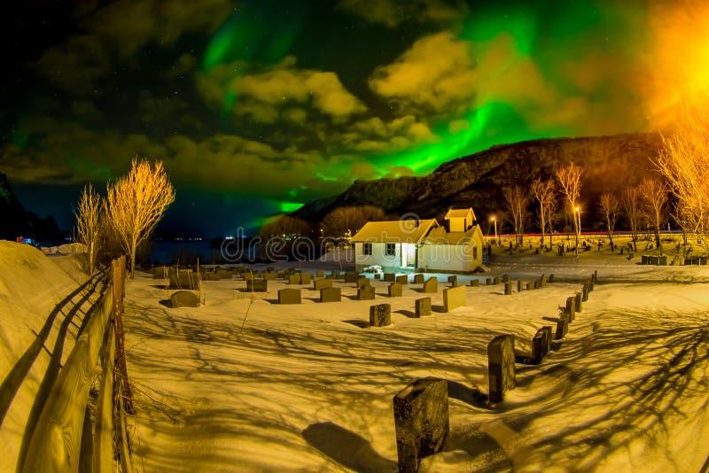 Den utomhus- sikten av vit stenade huset med många gravstenar som täcktes med snö, och härliga nordliga ljus skiner ljust och arkivfoton