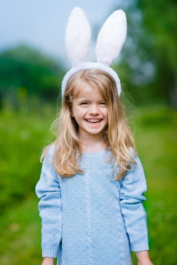 Den utomhus- ståenden av den härliga le vita kaninen för lilla flickan gå i ax royaltyfri foto