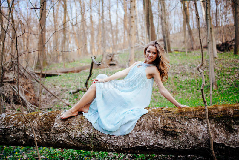 Den utomhus- ståenden av en härlig brunettmodell i blått klär på våren skogen fotografering för bildbyråer