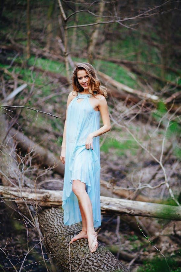 Den utomhus- ståenden av en härlig brunettmodell i blått klär på våren skogen arkivbild
