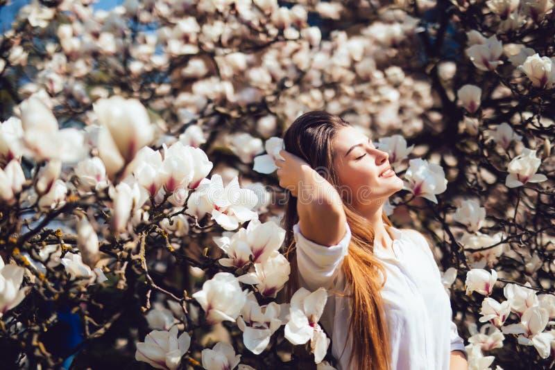 Den utomhus- ståenden av en ung härlig kvinna nära magnoliaträd med blommor får solbadet Flicka som bär stilfull kläder Kvinnlig  royaltyfri fotografi