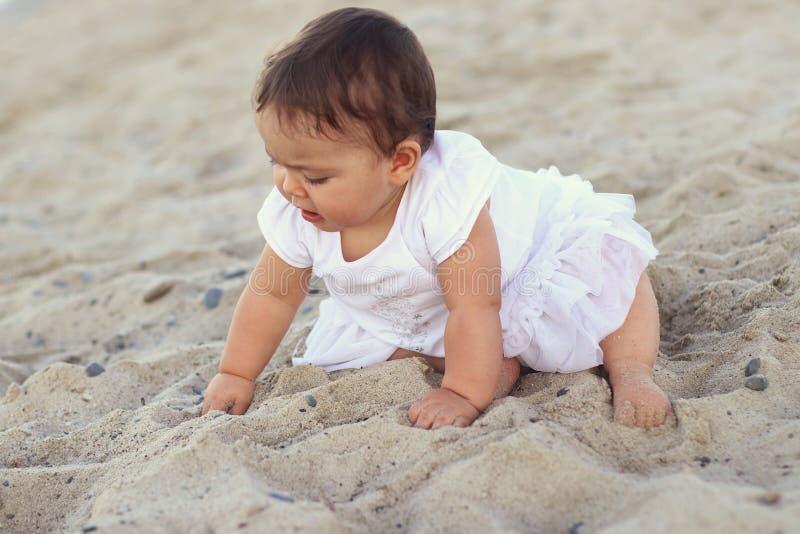 Den utomhus- ståenden av ett härligt behandla som ett barn på alla fours på sanden arkivfoton