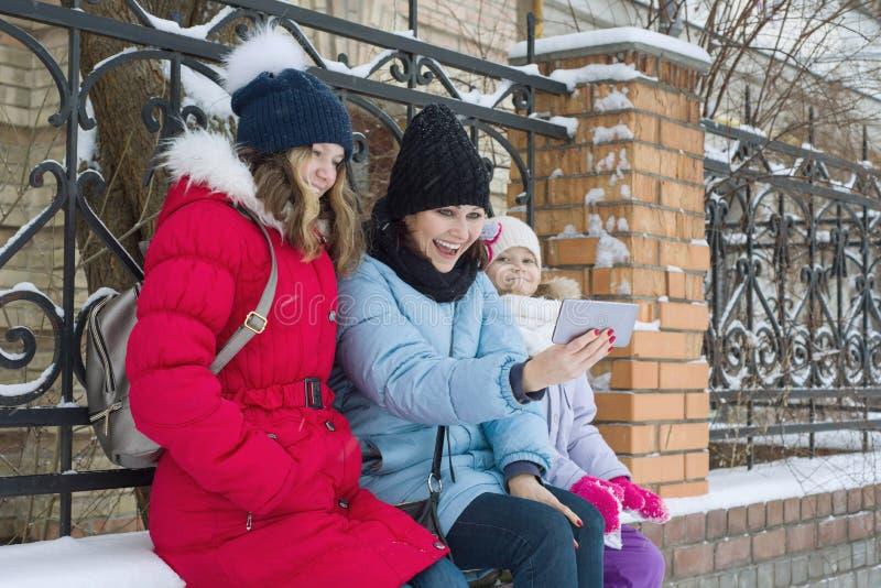 Den utomhus- vinterståenden av modern och två döttrar, familjen har gyckel i en snöstad som tar fotoet på mobiltelefonen fotografering för bildbyråer