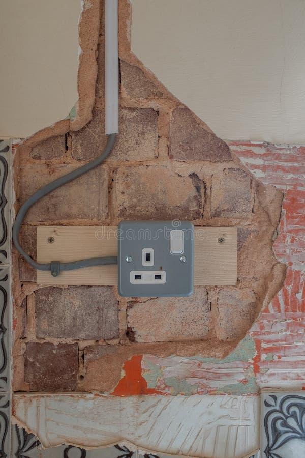 Den utsatta rappa visningen exponerade tegelstenarbete och ett elektriskt uttag och ledningsn?tet i v?ggen, i behov av reparation arkivbilder