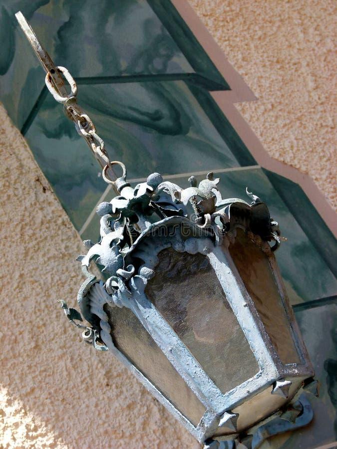 Den utsmyckade antika yttre lyktan hänger på en kedja i 45, den ° som kameran poserar royaltyfria bilder