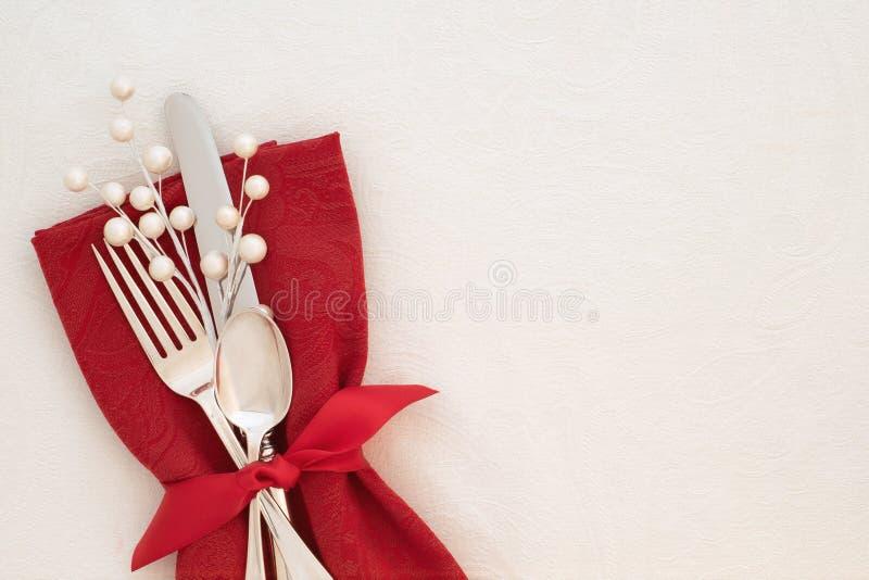 Den utsmyckade jultabellen förlägger inställningen med den röda servetten, bestick och vita bär på krämigt - vit borddukbakgrund  royaltyfri fotografi