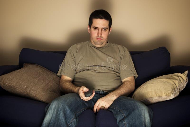 Den uttråkade överviktiga manen sitter på sofaen royaltyfri foto