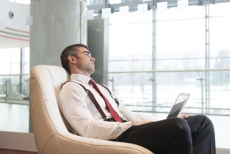 Den uttråkade affärsmannen stirrar ut fönstret royaltyfri fotografi