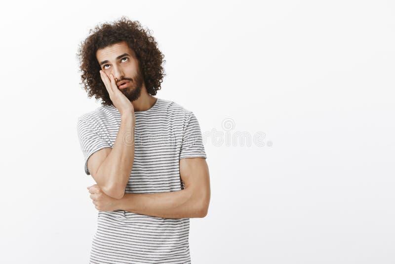 Den uttråkade likgiltiga stiliga latinamerikanska mannen med skägget och den afro frisyren som gör framsidan, gömma i handflatan  royaltyfria bilder