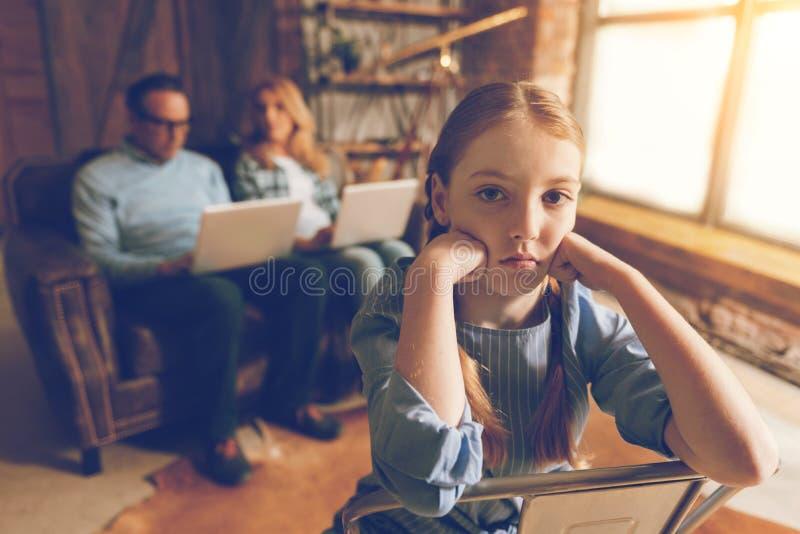 Den uttråkade lilla flickan på stol som väntar på upptaget arbete, uppfostrar royaltyfria bilder