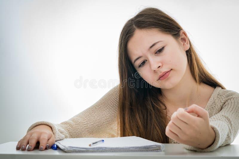 Den uttråkade tonåringflickan som kontrollerar henne, spikar, i stället för att studera fotografering för bildbyråer