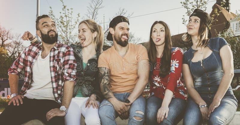 Den uttrycksfulla gruppen av vänner gör enfaldiga grimaser som sitter på en vägg i stadsmiljö royaltyfria foton