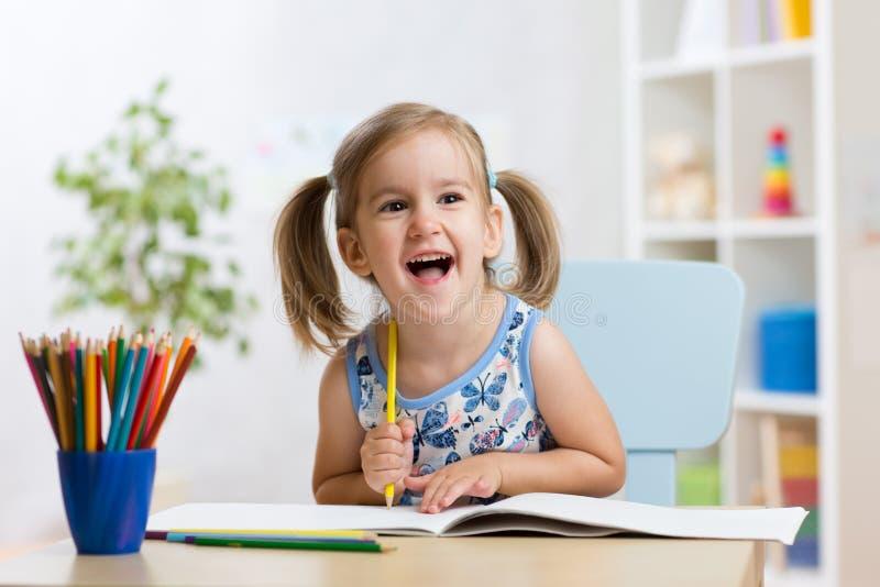 Den uttrycksfulla ungeflickan drar sammanträde på tabellen i rum i barnkammare arkivfoto